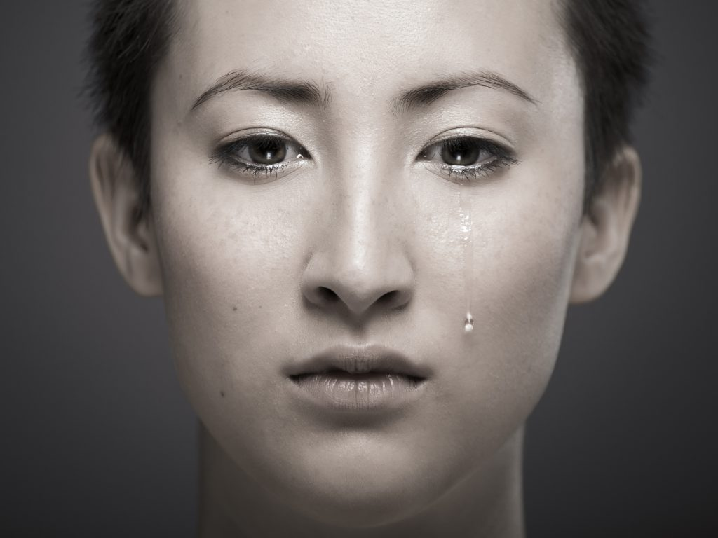 Portrait of young Asian girl with tear rolling down cheek