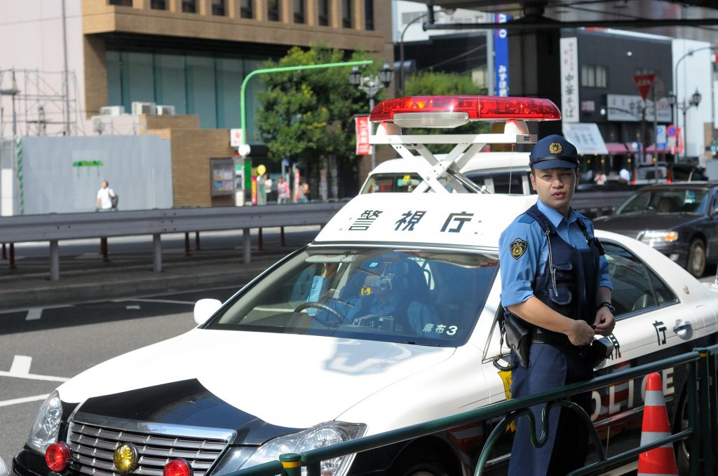 Tokyo pliceman in front of the police car