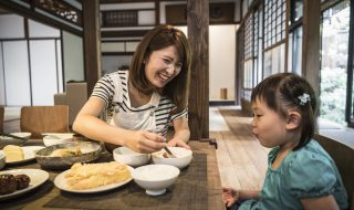 Young Japanese girl sitting at table with mother eating dinner, mother smiling, daughter watching